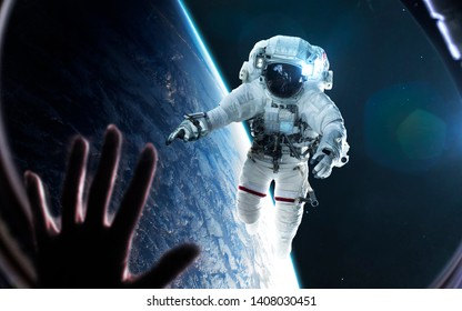 Woman looks at astronaut through the spaceship porthole. Elements of this image furnished by NASA