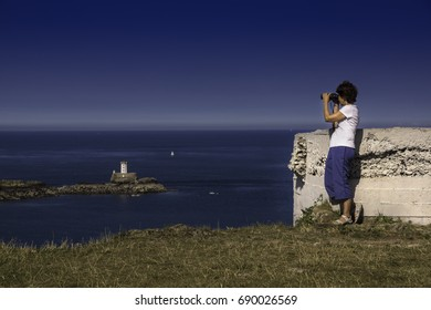 Woman looks with binoculars at the lighthouse