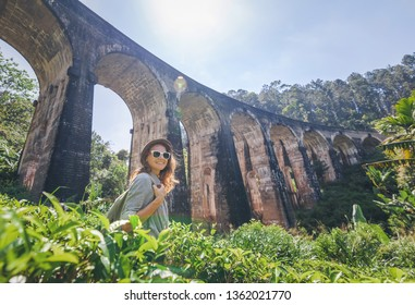 Woman looks at the Demodara nine arches bridge the most visited sight of Ella town in Sri Lanka, Travel to Asia