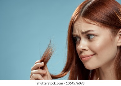 woman looks at distressed hair, care