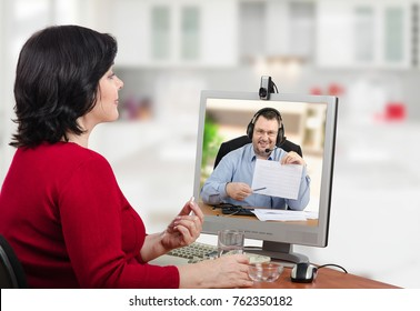 Woman looks at e-health cardiologist in her desktop monitor holding white pill in left hand. Businesswoman in red knitwear shirt prefers to take medicine under telemedicine supervision