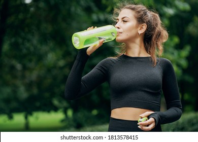 the woman looks great, athletic body, drinking water after a workout, the feeling of thirst. Portrait of a Caucasian woman, sweet, strong, confident