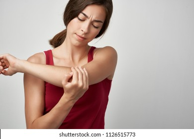 a woman looks at her elbow, bruised pain