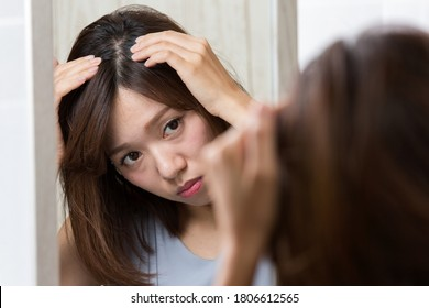 A woman looks at her scalp in the mirror.