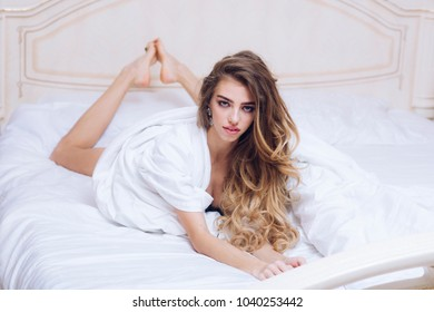 Woman looks hot in bathrobe after wellness and skin care procedures. Luxury wellness concept. Girl with mysterious face and long curly hair lays on white sheets. Lady with make up relaxing on bed.