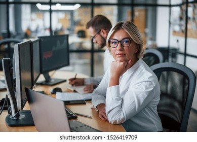 Woman looks into the camera. Two stockbrokers in formal clothes works in the office with financial market.