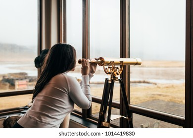 A woman looks into the distance through a telescope