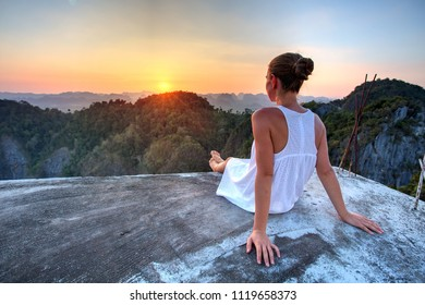 Woman looks at Krabi province from top of the hill at the Tiger Cave Monastery at sunset, Thailand