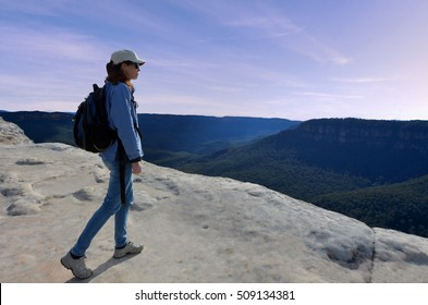 Woman looks at the landscape from Lincoln Rock Lookout at sunset in the Blue Mountains National Park in the Blue Mountains region of New South Wales, Australia