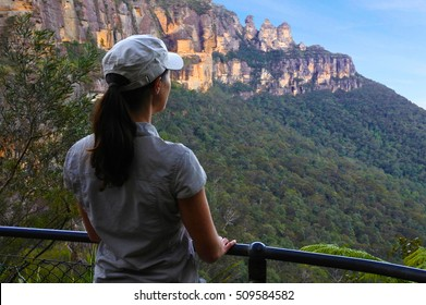 Woman looks at the landscape of The Three Sisters rock formation in the Blue Mountains of New South Wales, Australia, on the north escarpment of the Jamison Valley during sunset.
