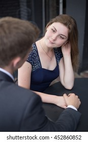 woman looks at a man in a cafe