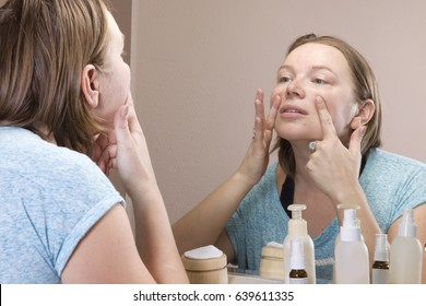 The woman looks in the mirror. Squeezes out pimples. Problems with the skin, hormonal changes.