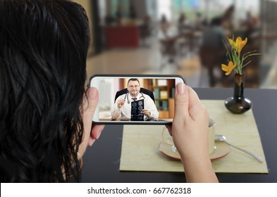 Woman looks at mobile phone sitting at a cafe table with her back to camera. In touchscreen, male telemedicine specialist reviewing brain x-ray image. Horizontal indoors shot on blurred background