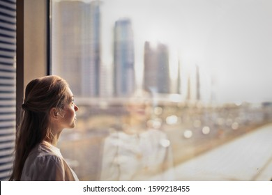 woman looks at a modern city from the window