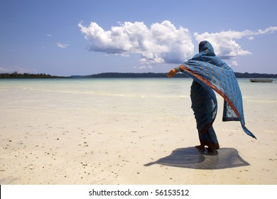 Woman looks out over the ocean enjoying the breeze wearing an Indian Saree.