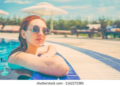 Woman looks out of the pool, hanging on the railing on the background of sun beds with umbrellas. Female swimming in the pool. Young woman relaxing in the water . Toned