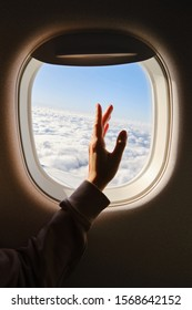 Woman looks out the window of an airplane. Hand near the porthole. Girl on the plane. Airplane wing, scenic view. Beautiful cloud, blue sky. Traveling by plane, adventure. Air transport. Aviation