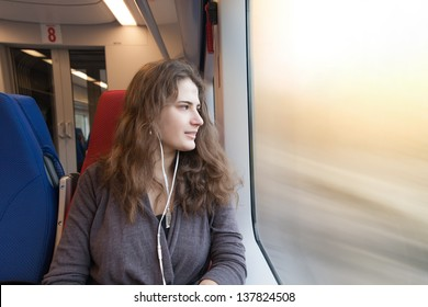 woman looks out the window while sitting in the train.