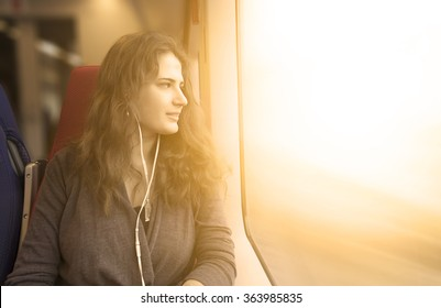 woman looks out window while sitting in the train.