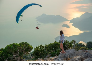 A woman looks at a paraglider, which hovers near the mount Babadag