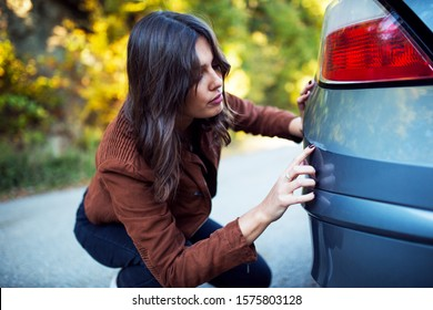 Woman looks at the scratch on her car