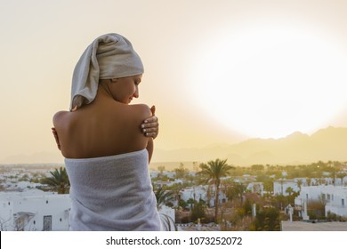 A woman looks at the setting sun with a towel on her head after a shower on a terrace overlooking the mountains.