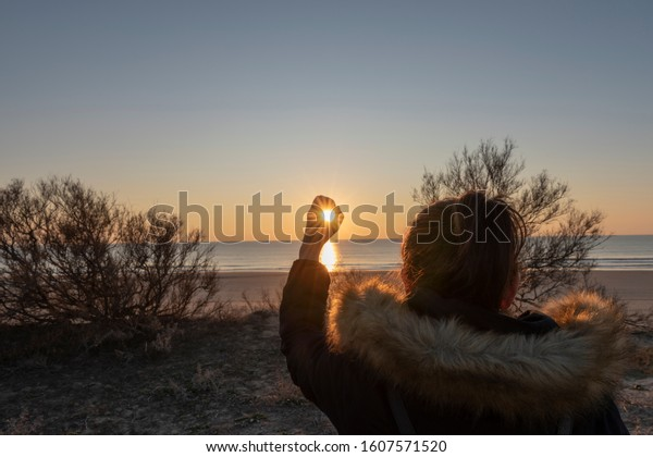A woman looks at the sun between her fingers