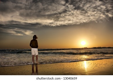 Woman looks at sunrise standing in water on beach. Shot in Sodwana Bay Nature Reserve, KwaZulu-Natal province, Southern Mozambique area, South Africa.