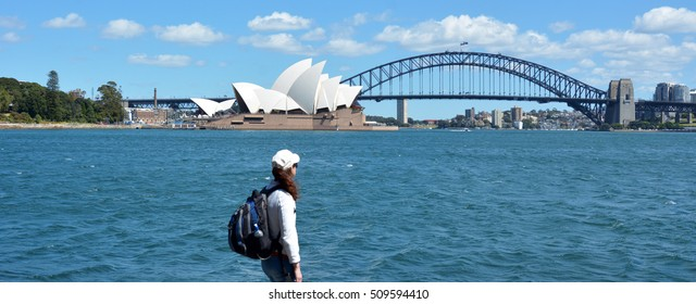 Woman looks at Sydney Harbor skyline in New South Wales, Australia.
