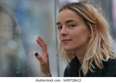 Woman looks through wet glass on a rainy day