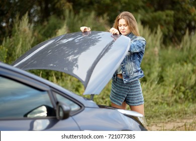 a woman looks under the hood of a car