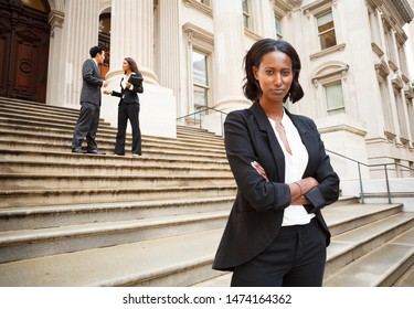 A woman looks at viewer while two well dressed professionals are in discussion on the exterior steps of a building. Could be lawyers, business people etc.