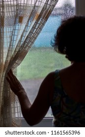 A woman looks at the window as it rains. Drops of rain on the window glass