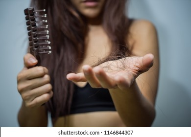 Woman loosing hair holding comb. Young girl losing hair problem, falling hair on brush. Treated healthy medical treatment hair lost concept.