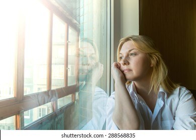 The woman lost in thought looking out the window. Sunny morning.