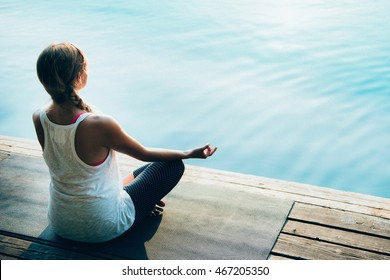 Woman in lotus positio, meditating, practicing yoga by the lake, calm water surface