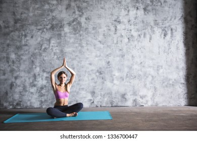Woman in the lotus position. Portrait of young happy girl practicing yoga.
