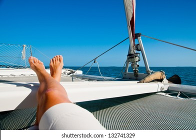 woman lounging on a catamaran sailboat trampoline with her feet propped up and crossed.  calm blue ocean and cloudless sky are in the background. copy space available