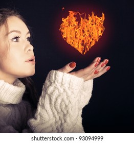 Woman in love with a burning heart in her hands.
