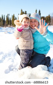 Woman and lovely toddler girl together in snow