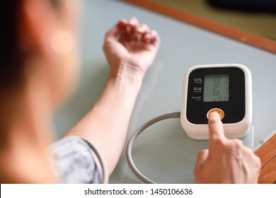 Woman with low blood pressure measuring with an electronic measurement device at home