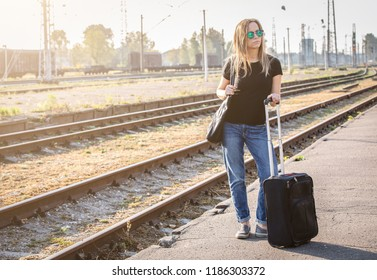 Woman with luggadge waiting on railway station for train on sunny day, going for travel or business meeting