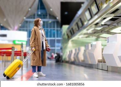 Woman with luggage stands at almost empty check-in counters at the airport terminal due to coronavirus pandemic/Covid-19 outbreak travel restrictions. Flight cancellation.Quarantine all over the world - Shutterstock ID 1681005856