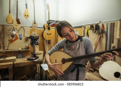 woman luthier testing the sound of an arabian buzuk, or bouzouki, in her musical instrument workshop