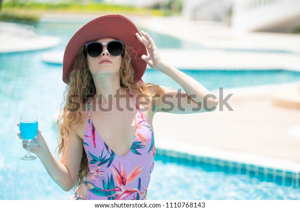 Woman in luxury beach hotel wearing swimsuit at swimming pool near tropical beach. Luxury lifestyle and hotel travel concept.