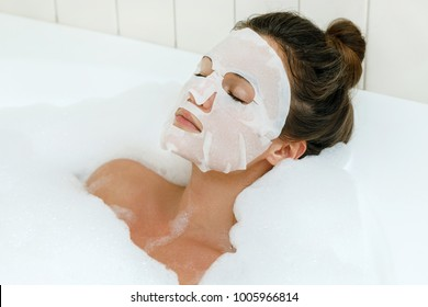 Woman lying in bathtub with a sheet mask on her face