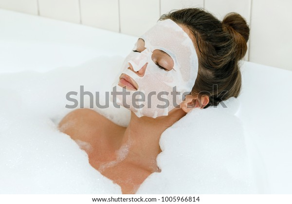 顔に覆面を付けて湯船に横たわる女性