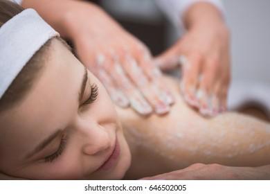 Woman lying at beautician's during exfoliating sugar scrub massage