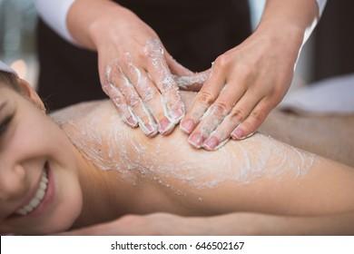 Femme allongée à l'esthéticienne pendant un massage gommage au sucre