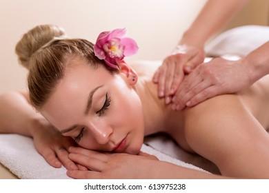 Woman lying in a beauty parlor, enjoying relaxing back massage